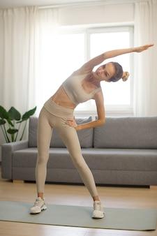 Mulher esportiva em forma se exercitando e treinando em casa