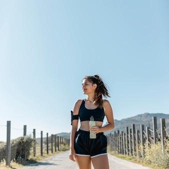 Mulher esportiva em pé na estrada com garrafa de água