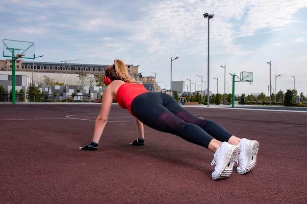 Mulher esportiva em roupas de alongamento, fazendo atividade de aquecimento na terra.