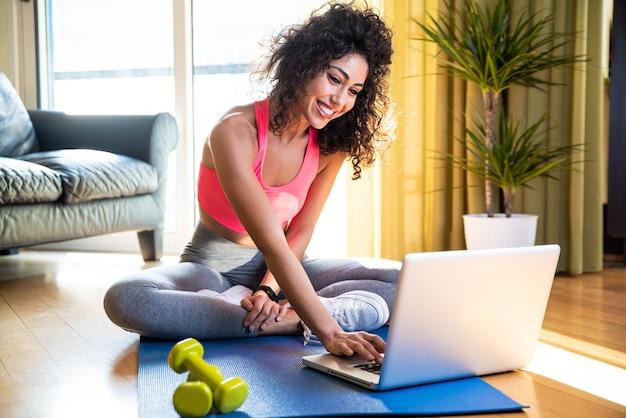 Mulher esportiva em roupas esportivas está sentada no chão com halteres usando um laptop na sala de estar