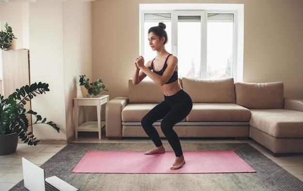 Mulher esportiva em roupas esportivas usando laptop e treinando as pernas no tapete de ioga em casa