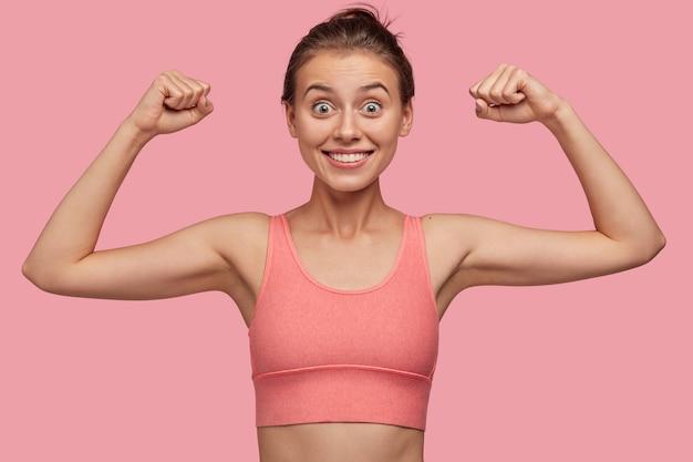 Mulher esportiva, enérgica e atlética posando contra a parede rosa
