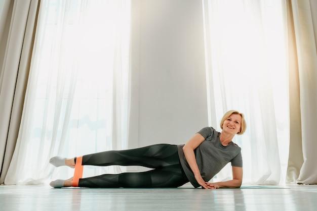 Mulher esportiva faz exercícios de aquecimento em casa com elástico