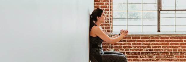 Mulher esportiva fazendo agachamento contra a parede
