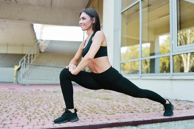 Mulher esportiva fazendo alongamento de perna antes de correr no ambiente urbano