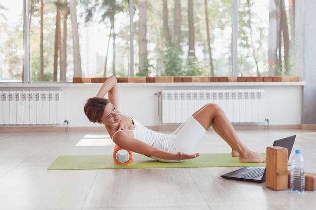 Mulher esportiva fazendo exercícios online com o rolo de espuma nas costas online com laptop
