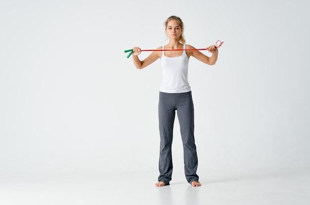 Mulher esportiva fazendo exercícios, pulando corda nas mãos, motivação de energia