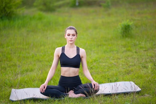 Mulher esportiva fazendo ioga e um estilo de vida saudável na natureza