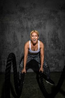 Mulher esportiva fazendo uma corda de batalha em uma academia