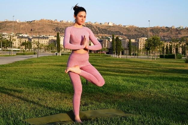 Mulher esportiva feliz praticando ioga ao ar livre