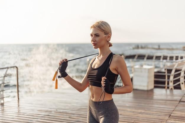 Mulher esportiva kickboxer com as mãos enfaixadas em bandagens e posando de pular corda