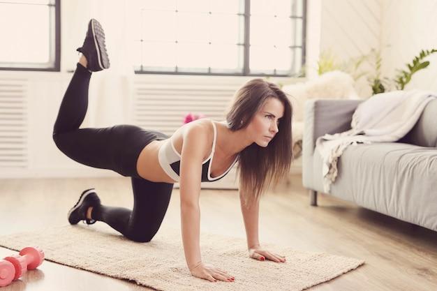 Mulher esportiva malhando em casa