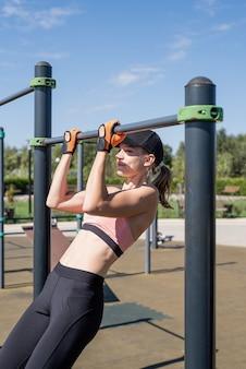 Mulher esportiva malhando na quadra de esportes em um dia ensolarado de verão