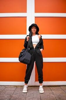 Mulher esportiva moderna e elegante segurando uma sacola de ginástica e encostada em uma parede laranja brilhante