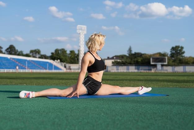 Mulher esportiva na esteira fazendo pose de divisão