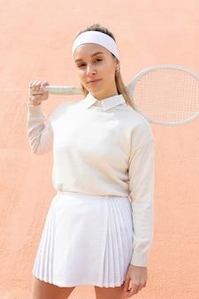 Mulher esportiva posando com raquete