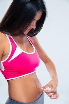 Mulher esportiva tocando a gordura da barriga