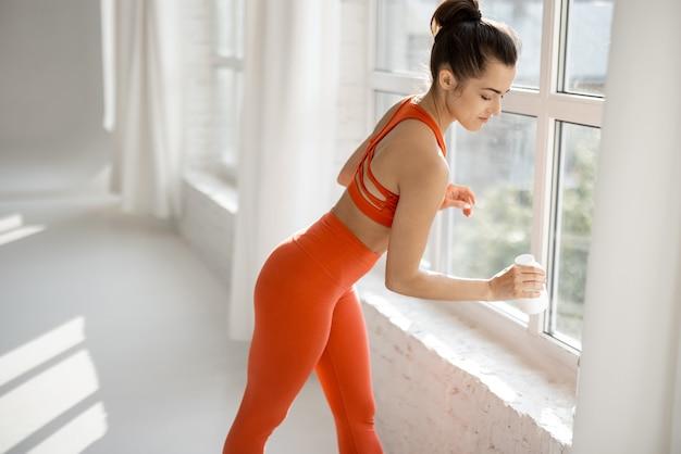 Mulher esportiva toma suplementos ou vitaminas na academia