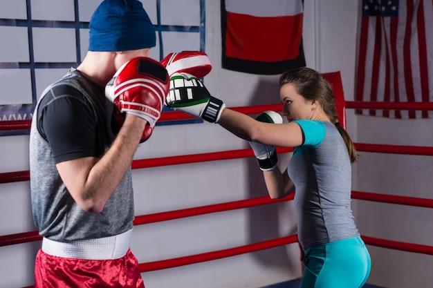 Mulher esportiva treinando kickboxing com o técnico em um ringue de boxe normal em uma academia
