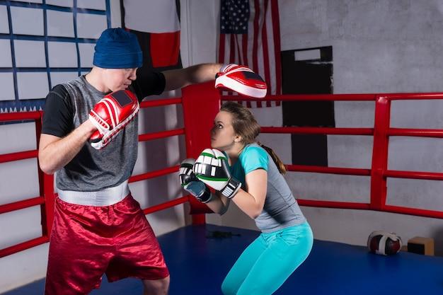 Mulher esportiva treinando kickboxing com o treinador em um ringue de boxe normal em uma academia