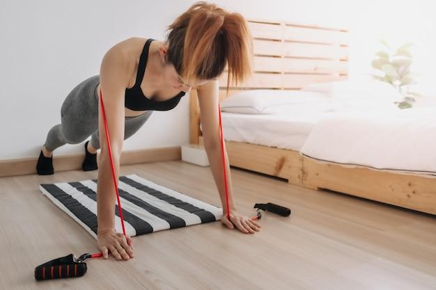 Mulher esportiva usa banda de resistência para exercícios no quarto