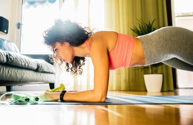 Mulher esportiva usando roupas esportivas, malhando em casa fazendo exercícios de tábuas