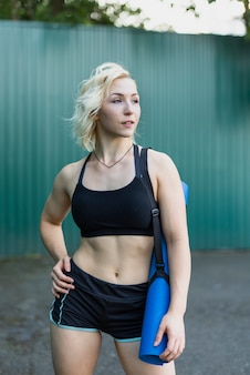 Mulher esportiva vista frontal com tapete de ioga