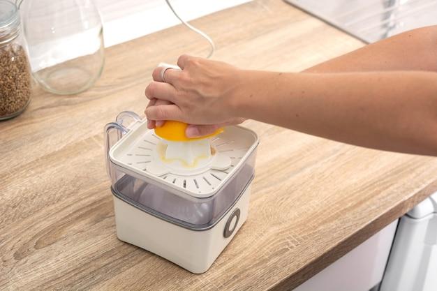 Mulher espremendo laranjas na cozinha