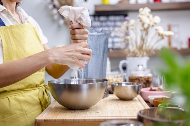 Mulher espremendo leite de amêndoa na cozinha de casa