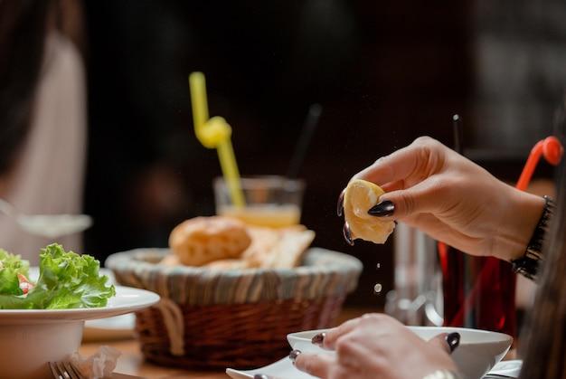 Mulher espremer limão à sopa na mesa de almoço