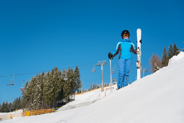 Mulher esquiadora na encosta de uma estação de esqui no inverno
