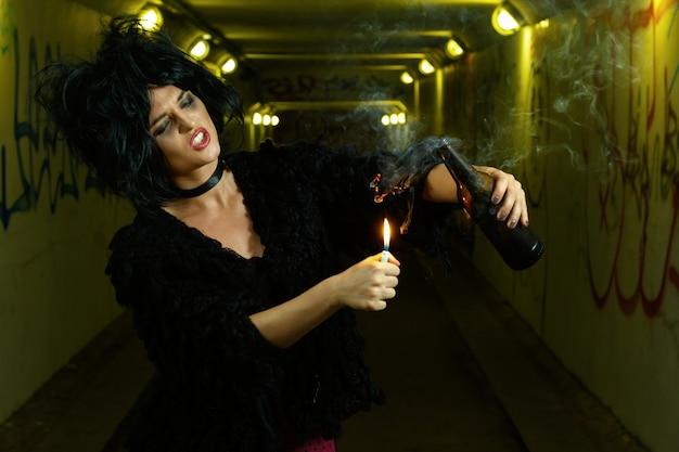 Mulher esquisita no túnel escuro com bomba de garrafa