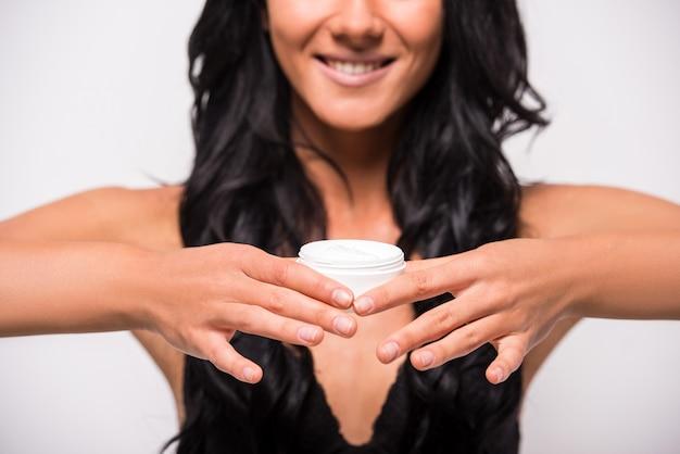 Mulher está a aplicar creme hidratante anti-rugas cuidados com a pele.