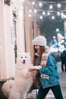 Mulher está abraçando seu cachorro em uma rua à noite