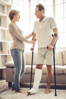 Mulher está ajudando seu marido bonito com a perna quebrada.