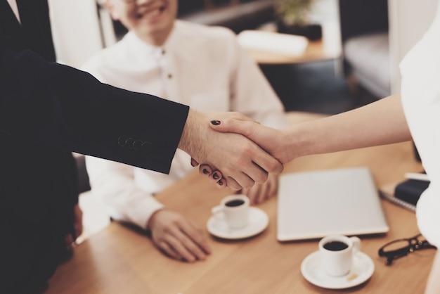 Mulher está apertando as mãos na entrevista de emprego.