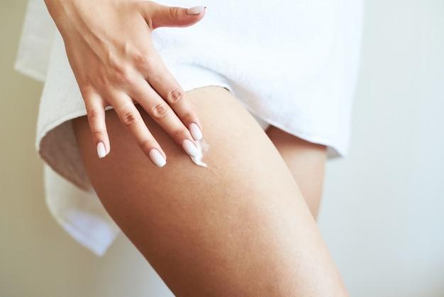 Mulher está aplicando creme na pele.