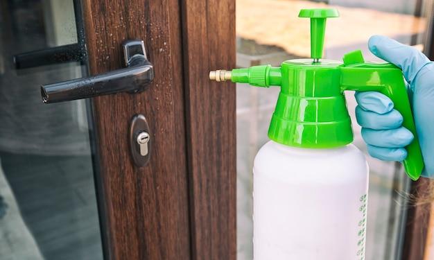 Mulher está aplicando desinfetante na maçaneta da porta