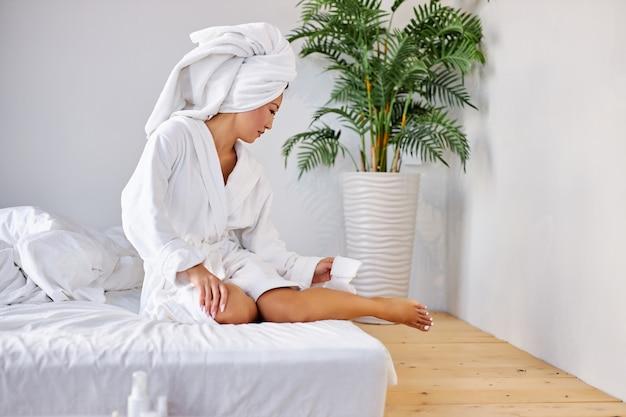 Mulher está aplicando o creme de cosméticos nas pernas, em casa, sentada na cama de roupão de banho. conceito de beleza