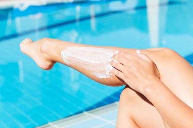 Mulher está aplicando protetor solar nas pernas bronzeadas à beira da piscina.
