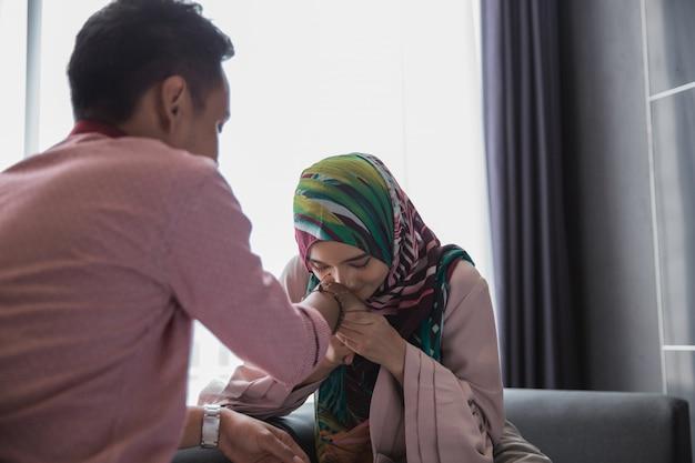 Mulher está beijando a mão do marido