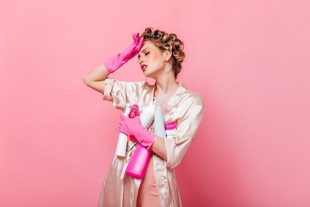 Mulher está cansada após a limpeza e posa com detergentes na parede rosa