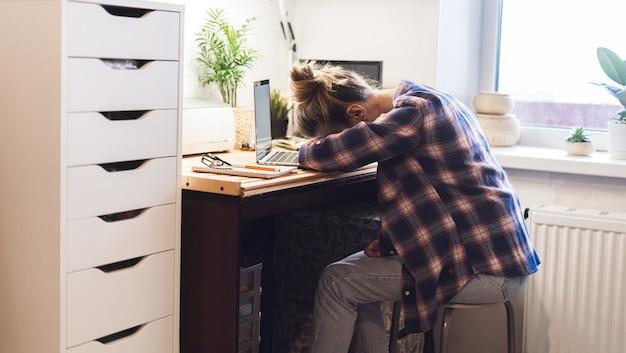 Mulher está cansada dormindo no teclado