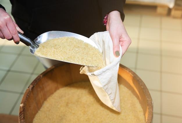Mulher está colocando arroz em uma sacola de compras reutilizável. pacotes ecologicamente e ecologicamente corretos. tecidos de lona e linho. salve o conceito de natureza. nenhum plástico de uso único em supermercados.
