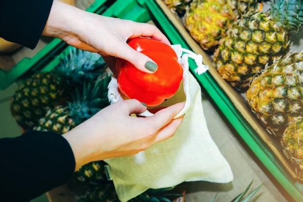 Mulher está colocando legumes em uma sacola de compras reutilizável. pacotes ecologicamente e ecologicamente corretos. tecidos de lona e linho. salve o conceito de natureza. nenhum plástico de uso único em supermercados.