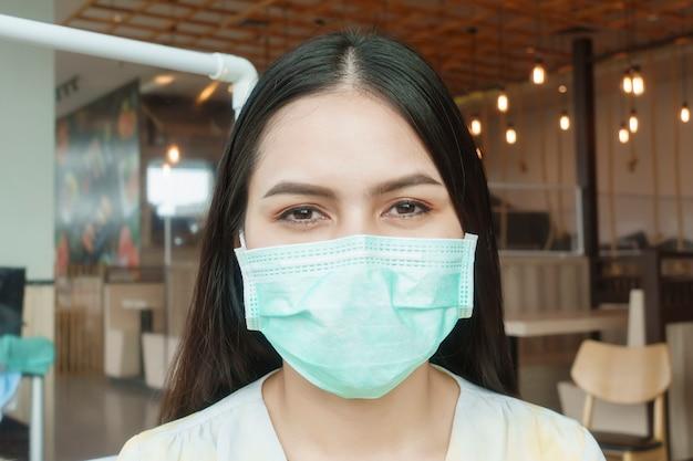 Mulher está comendo em restaurante com protocolo de distanciamento social enquanto cidade bloqueada devido a pandemia de coronavírus