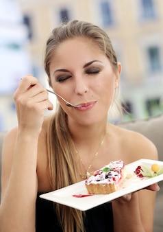 Mulher está comendo uma torta