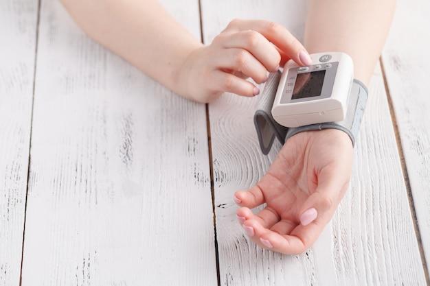 Mulher está cuidando da saúde com monitor de batimento cardíaco e pressão arterial