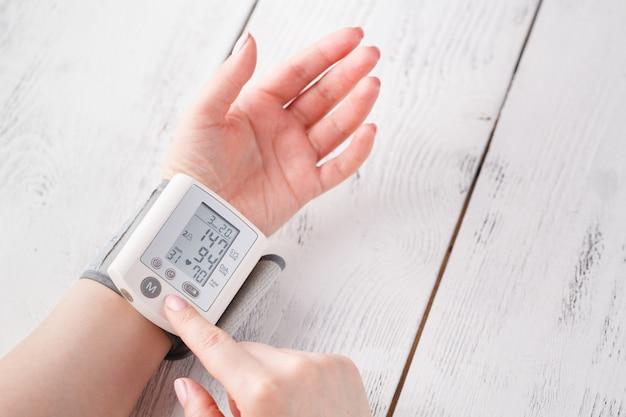 Mulher está cuidando da saúde com monitor de batimentos cardíacos e pressão arterial