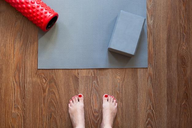Mulher está de pé descalço no chão na frente do tapete de ginástica e rolo